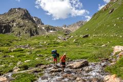 Πέρασμα του ποταμού βουνών με το σακίδιο πλάτης Στοκ Εικόνες