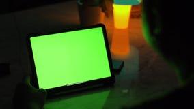 Πέρα από την άποψη ώμων του ασιατικού ατόμου που χρησιμοποιεί τον υπολογιστή ταμπλετών Πράσινη οθόνη του χρησιμοποίησης της τεχνο φιλμ μικρού μήκους