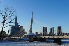 Πέρα από τον κόκκινο ποταμό Χειμερινή άποψη σχετικά με Esplanade τη γέφυρα RIEL με το καναδικό μουσείο για τα ανθρώπινα δικαιώματ στοκ φωτογραφία