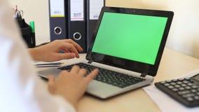 Πέρα από τον ώμο που πυροβολείται μιας γυναίκας που δακτυλογραφεί σε ένα lap-top με μια βασικός-πράσινη οθόνη απόθεμα βίντεο