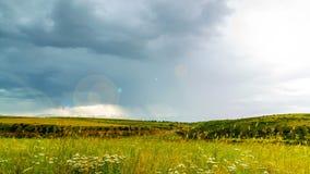 Πέρα από τους ανθίζοντας τομείς κολυμπήστε thunderclouds, ο ήλιος εμφανίζεται και φωτίζει όλα με το φως 4K Timelaps φιλμ μικρού μήκους