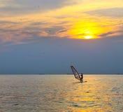 πέρα από το ηλιοβασίλεμα σκιαγραφιών θάλασσας windsurfer Στοκ Εικόνες