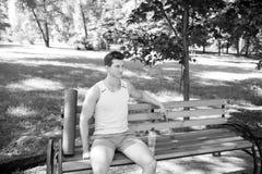 πέρα από το workout Το άτομο με το χαλί γιόγκας και το μπουκάλι νερό κάθονται στον πάγκο στο πάρκο Ενώστε υπαίθρια την πρακτική γ στοκ εικόνα με δικαίωμα ελεύθερης χρήσης