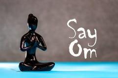 Πέστε το OM - ενθαρρυντικό μήνυμα κοντά στο ειδώλιο της νέας γυναίκας meditates εν ενεργεία τη γιόγκα Έννοια ελευθερίας και χαλάρ Στοκ Εικόνες
