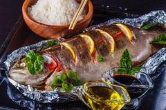 Πέστροφα που ψήνεται στο φύλλο αλουμινίου με το λεμόνι και τα χορτάρια με ένα πιάτο του ρυζιού και τις σάλτσες σε ένα παλαιό φύλλ Στοκ Εικόνες