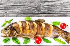 Πέστροφα fishe που ψήνεται με το λεμόνι, ντομάτες Στοκ Εικόνα