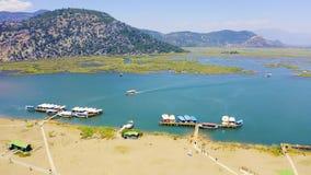 Πέταγμα πέρα από τον ποταμό Dalyan Ο αμμώδης οβελός Iztuzu χωρίζει τον ποταμό και τη θάλασσα Βάρκες τουριστών που δένονται κοντά  απόθεμα βίντεο