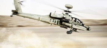Πέταγμα πολεμικών σκαφών ελικοπτέρων τόξων Apache επίθεσης γρήγορο και χαμηλό με τα συντρίμμια σκόνης στα ίχνη του Στοκ Εικόνες