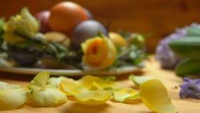 Πέταλα της ροδαλής πτώσης σε έναν πίνακα σε ένα κλίμα των χρωματισμένων αυγών Πάσχας απόθεμα βίντεο