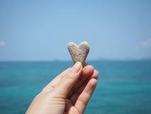 Πέτρα μορφής καρδιών εκμετάλλευσης χεριών πέρα από το υπόβαθρο θερινών παραλιών Στοκ εικόνα με δικαίωμα ελεύθερης χρήσης