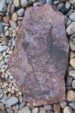 Πέτρα χαλικιών χρώματος στο υπόβαθρο με τον επίπεδο βράχο στη μέση Στοκ φωτογραφίες με δικαίωμα ελεύθερης χρήσης