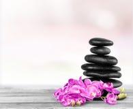 Πέτρες και λουλούδια βασαλτών της Zen στο ξύλινο υπόβαθρο Στοκ εικόνα με δικαίωμα ελεύθερης χρήσης