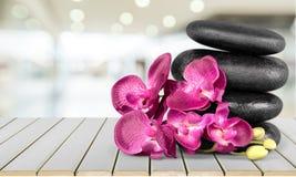 Πέτρες και λουλούδια βασαλτών της Zen στο ξύλινο υπόβαθρο Στοκ εικόνες με δικαίωμα ελεύθερης χρήσης