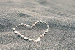 Πέτρες με μορφή της καρδιάς στη μαύρη αμμώδη παραλία Στοκ Εικόνες