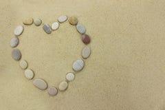 Πέτρες παραλιών με μορφή μιας καρδιάς σε μια αμμώδη παραλία Στοκ Εικόνες