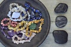 Πέτρες πολύτιμων λίθων και κρύσταλλα σε ένα ξύλινο υπόβαθρο με τα χαλίκια τύμβων Στοκ Εικόνες