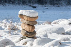 Πέτρες στην ισορροπία στη χειμερινή ακτή κάτω από το χιόνι Στοκ Εικόνα