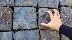 Πέτρινα τούβλα βράχου πίσω από το φράκτη μετάλλων με το αρσενικό υπόβαθρο ταπετσαριών τοίχων χεριών Κλείστε επάνω των αρσενικών ο στοκ εικόνες
