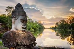 Πέτρινα Asura και ηλιοβασίλεμα πέρα από την τάφρο που περιβάλλει Angkor στην Καμπότζη Στοκ εικόνα με δικαίωμα ελεύθερης χρήσης