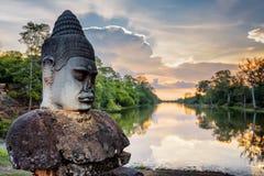 Πέτρινα Asura και ηλιοβασίλεμα πέρα από την τάφρο που περιβάλλει Angkor, Καμπότζη Στοκ Εικόνα