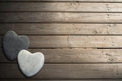 Πέτρινες καρδιές στον ξύλινο θαλάσσιο περίπατο με την άμμο Στοκ Φωτογραφίες