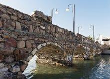 Πέτρινη γέφυρα πέρα από έναν ποταμό προοπτικής κινηματογραφήσεων σε πρώτο πλάνο Στοκ Εικόνες