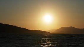 Πέτρινη παραλία, πορεία ήλιων, σκιαγραφίες των νησιών, ηλιοβασίλεμα απόθεμα βίντεο