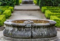 Πέτρινη πηγή νερού στη μέση ενός όμορφου κήπου Στοκ εικόνα με δικαίωμα ελεύθερης χρήσης