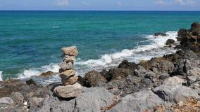 Πέτρινη πυραμίδα στη δύσκολη ακτή της Κρήτης ενάντια στην μπλε θάλασσα απόθεμα βίντεο