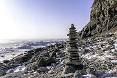 Πέτρινη πυραμίδα το χειμώνα σε μια δύσκολη παραλία του παγωμένου κόλπου που καλύπτεται με το χιόνι Στοκ εικόνα με δικαίωμα ελεύθερης χρήσης