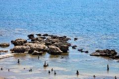 Πέτρινη πυραμίδα χαλικιών στο μπλε θαλάσσιο νερό στην ηλιόλουστη ακτή το καλοκαίρι Στοκ φωτογραφίες με δικαίωμα ελεύθερης χρήσης