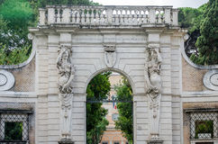 Πέτρινη πύλη για να εισαγάγει το πάρκο με τις στήλες υπό μορφή ανθρώπινης γυναίκας με μια κάλυψη των όπλων και της πίστης στην πρ Στοκ εικόνα με δικαίωμα ελεύθερης χρήσης
