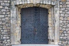 Πέτρινη σύσταση τοίχων με τη μεσαιωνική πόρτα Στοκ φωτογραφία με δικαίωμα ελεύθερης χρήσης