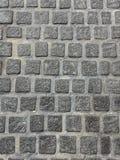Πέτρινος τοίχος τούβλων στην επίγεια λαβή από το τσιμέντο Στοκ Εικόνες