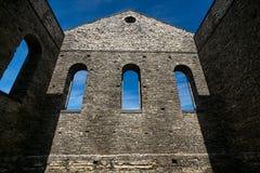 Πέτρινος τοίχος των αρχαίων καταστροφών εκκλησιών με τα γοτθικά παράθυρα Στοκ φωτογραφία με δικαίωμα ελεύθερης χρήσης