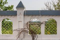 Πέτρινος φράκτης ενός ορθόδοξου μοναστηριού με τα παράθυρα δικτυωτού πλέγματος και μια άμπελο Στοκ Εικόνες