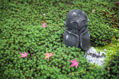 Πέτρινο άγαλμα Jizo στο έδαφος που καλύπτεται από το πράσινο βρύο αστεριών και τα κόκκινα φύλλα σφενδάμου κατά τη διάρκεια του φθ στοκ εικόνα