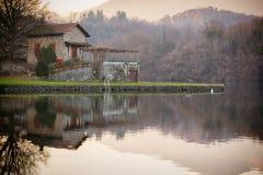 Πέτρινο εξοχικό σπίτι στη λίμνη, καφετιά χρώματα, ειρηνική ατμόσφαιρα Στοκ Φωτογραφία