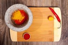 Πέτρινο κονίαμα με τη σκόνη πάπρικας Καρύκευμα στα τέμνοντα τσίλι και Habanero μορίων πινάκων καυτά Μαγειρική σύνθεση στο ξύλινο  Στοκ Εικόνες