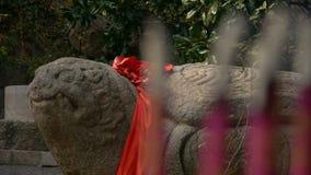 Πέτρινο τοτέμ χελωνών με την κόκκινη κορδέλλα, θυμίαμα καψίματος στον καυστήρα θυμιάματος, αέρας του καπνού απόθεμα βίντεο