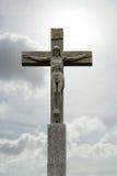 Πέτρινο crucifix με το Ιησούς Χριστό πριν από το νεφελώδη ουρανό Στοκ Εικόνες