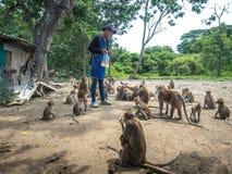 Πίθηκος που περιμένει το καλαμπόκι από τους ανθρώπους που δίνουν στοκ φωτογραφίες