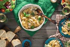 Πίνακας γευμάτων με τα ζυμαρικά, τη σαλάτα και το κρασί στον ξύλινο πίνακα Στοκ φωτογραφία με δικαίωμα ελεύθερης χρήσης