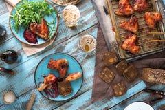 Πίνακας γευμάτων με τα φτερά και την μπύρα κοτόπουλου Στοκ Εικόνα