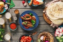 Πίνακας γευμάτων με το ψημένο στη σχάρα λουκάνικο, tortilla, μπύρα και διαφορετικός Στοκ φωτογραφίες με δικαίωμα ελεύθερης χρήσης