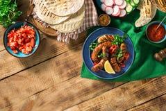 Πίνακας γευμάτων με το ψημένο στη σχάρα λουκάνικο, tortilla περικαλύμματα και διαφορετικός Στοκ Φωτογραφία