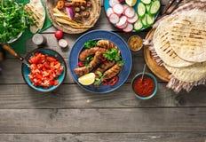 Πίνακας γευμάτων με το ψημένο στη σχάρα λουκάνικο, tortilla περικαλύμματα και διαφορετικός Στοκ Εικόνες