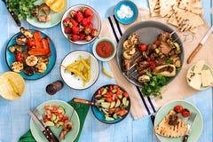 Πίνακας γευμάτων με το shish kebab, ψημένα στη σχάρα λαχανικά, σαλάτα, πρόχειρα φαγητά Στοκ Εικόνα
