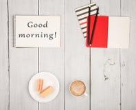 Πίνακας γραφείων με τα σημειωματάρια και το κείμενο & x22 Καλημέρα! & x22 , φλιτζάνι του καφέ και βάφλες στοκ εικόνες