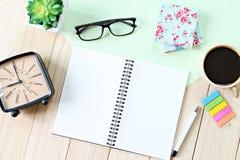 Πίνακας γραφείων γραφείων με το ανοικτά έγγραφο σημειωματάριων, τα εξαρτήματα και το φλυτζάνι καφέ Στοκ Φωτογραφία